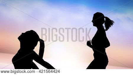 Composition of silhouette of fit women running and stretching against clouds on blue to pink sky. sport, fitness and active lifestyle concept digitally generated image.