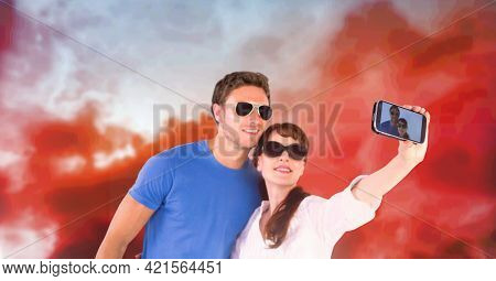 Composition of happy holiday couple in sunglasses smiling, taking selfie , over sunset sky. free time, holiday and leisure lifestyle concept digitally generated image.