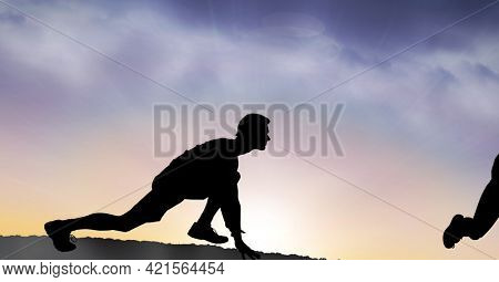 Composition of silhouette of fit man starting run against clouds on blue to pink sky. sport, fitness and active lifestyle concept digitally generated image.