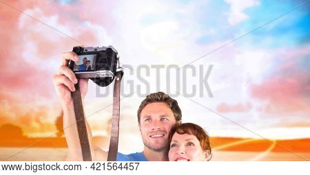 Composition of happy holiday couple couple smiling, taking selfie with slr camera, over sunset sky. free time, holiday and leisure lifestyle concept digitally generated image.