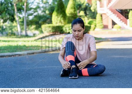 Portrait Of Healthy Young Woman Tying Running Shoes And Sitting On Street Before Running. Female Ath
