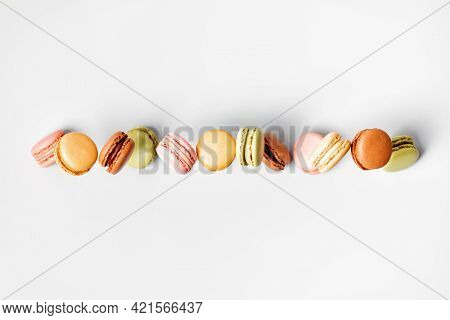 Vintage pastel colored French macaroons or macarons in motion falling on grey background. Macaron Sweets