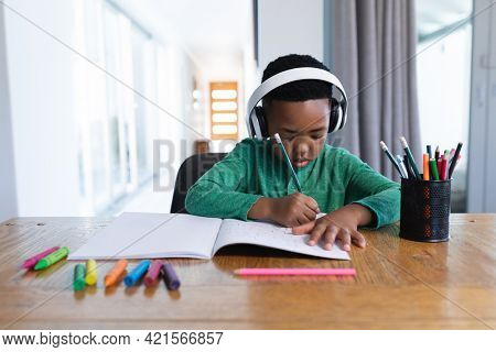 African american boy in online school class, using headphones and writing in his notebook. at home in isolation during quarantine lockdown.