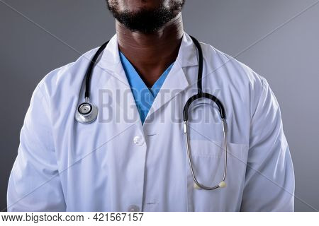 Mid section of african american male doctor wearing stethoscope against grey background. healthcare and medical professionalism concept