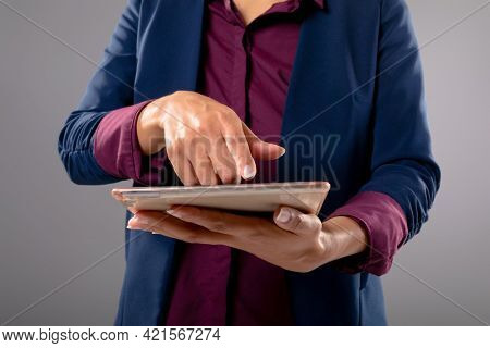 Mid section of businesswoman using digital tablet against grey background. business, professionalism and technology concept