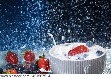 Milk Splash Close Up Of Falling Berries In A Grey Plate Of Milk. Strawberries And Blueberries Multiv