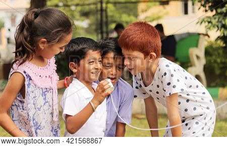 Group Of Children Having Fun By Playing With String Telephone During Holiday Summer Camp - Concept O