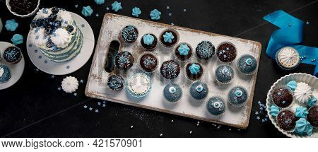 Delicious Cake And Cupcakes In Blue On Dark Background. Table Setting For Celebration.