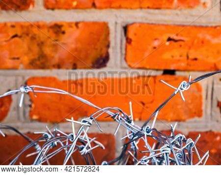 Barbed Wire On A Background Of A Red Brick Wall. Barbed Wire. Brick Wall. Red Bricks. Protection Of