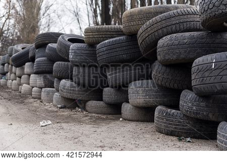 A Wall Made Of Old Wheels. Wall Made Of Old Car Tires. Fencing From Wheels. Fence On The Street.