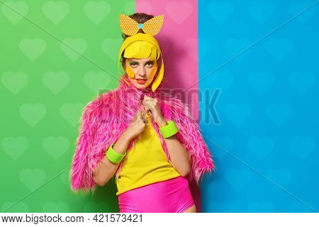 Bright style. Portrait of a fashionable beauty girl with colorful paper makeup and hairstyle on a fuchsia,  green and blue background. Party style. Makeup and cosmetics.