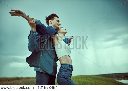 Beautiful romantic couple in love stand in a valley facing the wind against a stormy sky. Beauty, fashion. Denim style. Relationships.