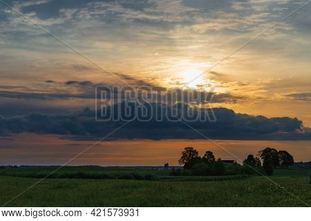 Morning Or Evening Clouds Sun And Field Among Trees In The Warm Summer Weather,nice Colored Evening