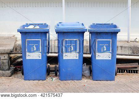 Three Blue Trash Placed Near The Wall.
