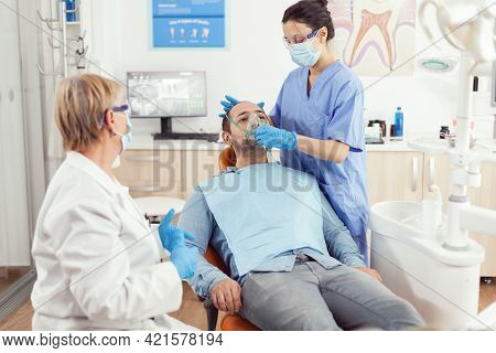 Stomatologist Nurse Putting Oxigen Mask Before Tooth Surgery Sitting On Dental Chair In Stomatology