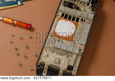 Computer Repair Services And Components Concept. Disassembled Computer Graphics Card On Brown Backgr