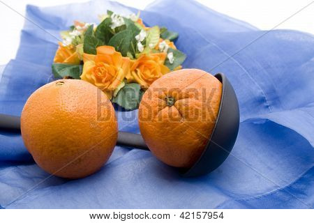 Fresh Ripe Tangerine with soup spoon on blue underlayment