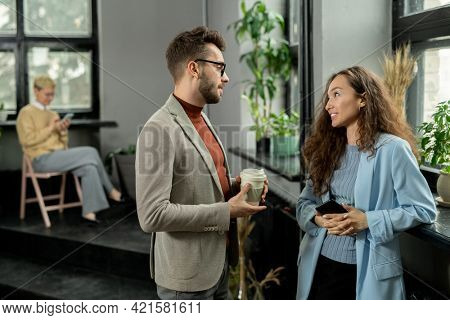 Two young managers talking at break in office environment