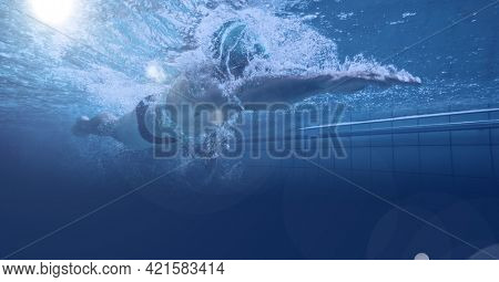 Composition of athletic man swimming in swimming pool over light blur. sport, fitness and active lifestyle concept digitally generated image.