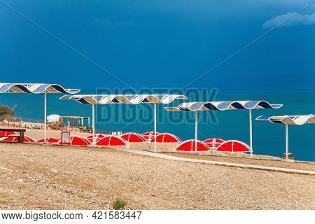 The Dead Sea is a closed salt lake. Israeli coast. The magnificent exotic resort for treatment and relaxation. Picturesque beach with bright sunshades. Gloomy sky with dark thunderclouds