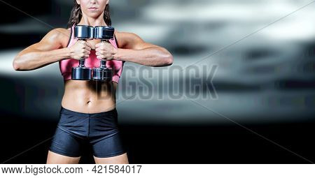 Composition of muscular woman exercising with dumbbells over black blur. sport, fitness and active lifestyle concept digitally generated image.