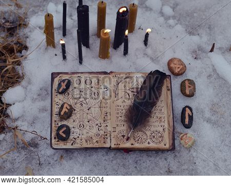 Top View Of Open Witch Book With Spells, Burning Candles And Runes Outside In Winter. Esoteric, Goth