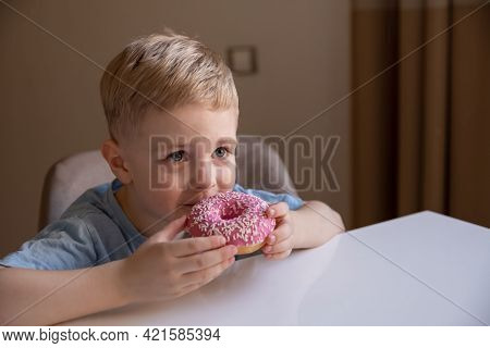 The Concept Is Useless Food. A Little Boy With Blond Hair Eats A Pink Doughnut At Home. He's Happy,