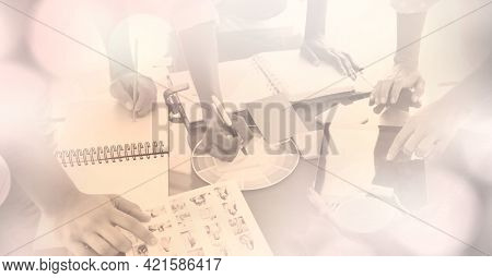 Composition of creative business people working together in office and spots of light. business professionals and teamwork concept digitally generated image.