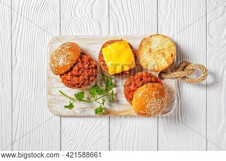 Sloppy Joe Sandwiches On Brioche Buns Served  On A White Wooden Board, Close-up, American Cuisine