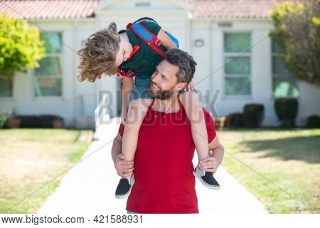 Parent And Pupil Of Primary School. Father Giving Son Piggyback Ride After Come Back From School.