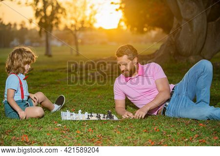 Father Play Chess With Son. Family Outside Game. Little Boy Play Chess With Parent. Cognitive Develo