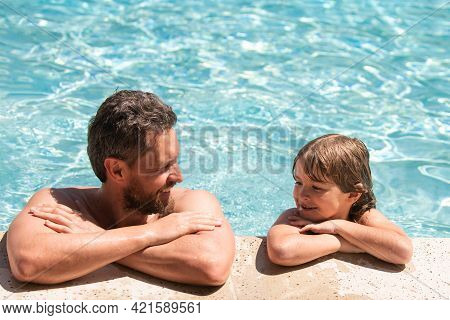 Father And Son In Pool. Child With Dad Playing In Swimming Pool. Pool Party. Sport Activity. Father
