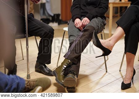 Legs of several people sitting on chairs in front of one another during session