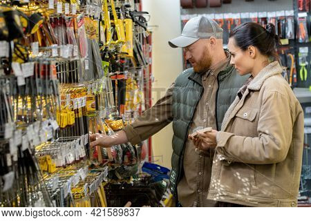 Man and woman choosing goods for home renovation in hardware store