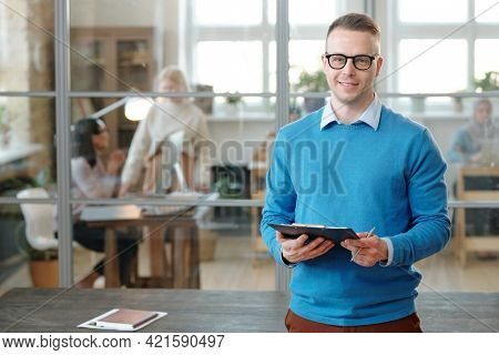 Portrait of smiling confident young Caucasian man in eyeglasses standing with clipboard against table in open space office