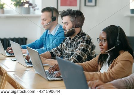 Group of concentrated young multi-ethnic call center agents sitting at tables and using laptops while selling products by phones