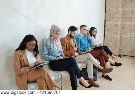 Group of serious young multi-ethnic job candidates in stylish outfits sitting in line at wall in corridor and wasting time while waiting for interview