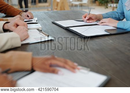Close-up of unrecognizable woman sitting at table in front of company representatives and signing contract with company after interview