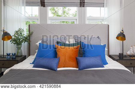 Blue And Orange Pillow On King Size Bed In Contemporary Bedroom With Modern Lamp  And Vase On Nights