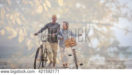 Composition of senior couple walking with bicycles on beach and autumn foliage. healthy active retirement lifestyle concept digitally generated image.