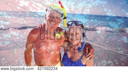 Composition of senior couple wearing swimming goggles, embracing on beach and autumn foliage. healthy active retirement lifestyle concept digitally generated image.