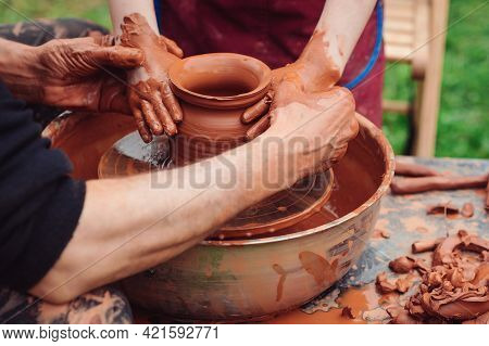 Potter Teaching Child To Make Ceramic Pot On The Pottery Wheel. Pottery Workshop Outside. Potters An