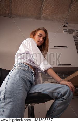 Portrait Of A Beautiful Blonde Girl In Simple Everyday Things Sitting Indoors.