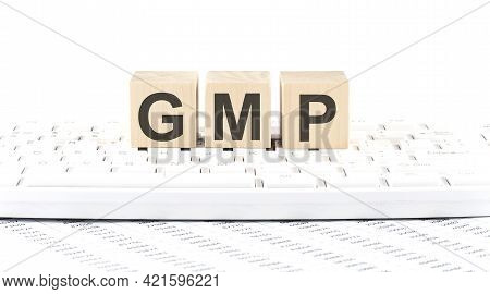 Gmp -word Wooden Block On Keyboard Background Witn Chart