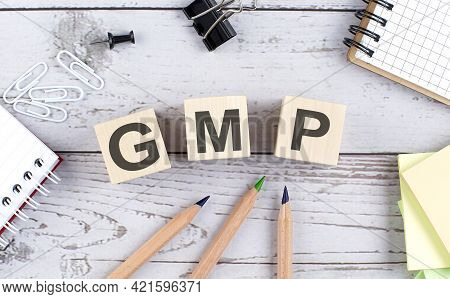 Gmp Text On Wooden Block With Office Tools On Wooden Background