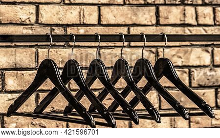 Fashionable Different Types Of Hanger. Many Wooden Black Hangers On A Rod. Wooden Coat Hanger Clothe