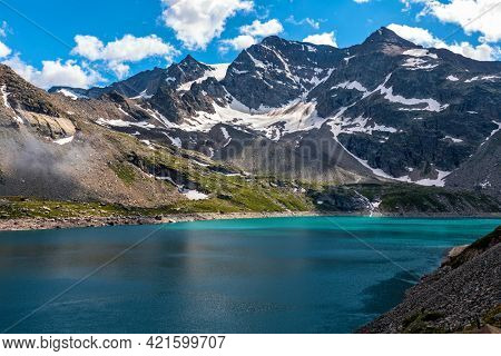 Small alpine lake with turquoise water and mountain ridge with snowy slopes on background in Piedmont, Northern Italy.