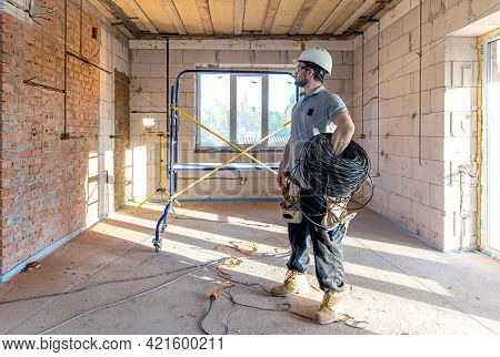 An Electrician Examines A Construction Drawing While Holding An Electrical Cable In His Hand At A Wo