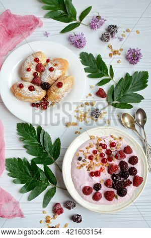 Yogurt With Berries And Granola And Croissants For Breakfast. Oatmeal With Raspberries, Hedgehogs An