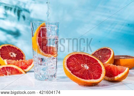 Refreshing Cocktail With Grapefruit On A Blue Background. A Glass Glass With Ice And Grapefruit Slic
